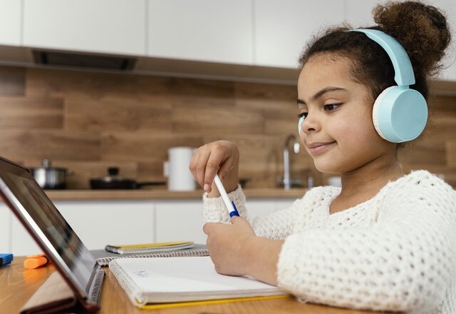 side_view_of_little_girl_during_online_school_with_tablet_and_headphones